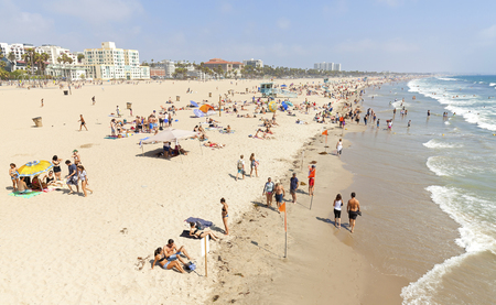 monica: Santa Monica, USA - August 22, 2015: People resting on beach during peak season. Santa Monica had become famous resort town by the early 20th century.