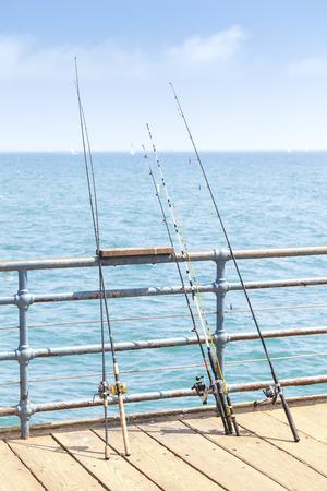 monica: Fishing rods on pier, Santa Monica, USA.