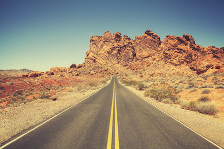 freedom nature: Retro stylized road through rocky desert in Valley of Fire State Park, Nevada. Stock Photo
