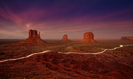 Car lights trails in Monument Valley at night, USA.