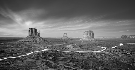 car lights: Black and white photo of the Monument Valley with car lights trails at night, USA.