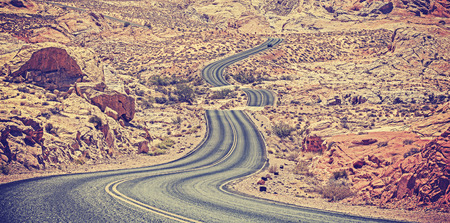 Vintage toned curved desert highway, travel adventure concept, USA. Stock Photo