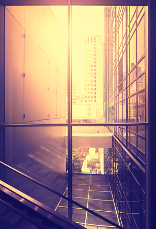 Vintage stylized picture of modern office at sunset, New York City, USA.