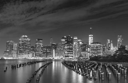 Black and white photo of Manhattan waterfront at night, New York City, USA.