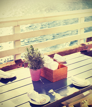 decoration: Vintage toned table setting on pier at sunset, California, USA.