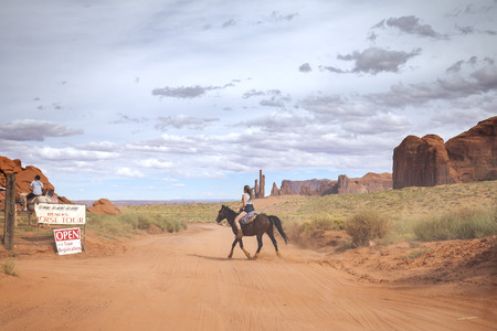 Utah, USA - September 7, 2015: Tourist riding horse in Navajo Nations Monument Valley Park with a guide, horse is an important aspect of the Navajo culture.