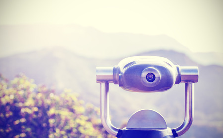 monocular: Vintage toned monocular pointed at horizon, shallow depth of field.