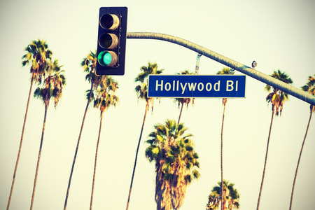 Cross processed Hollywood boulevard sign and traffic lights with palm trees in the background, Los Angeles, USA.