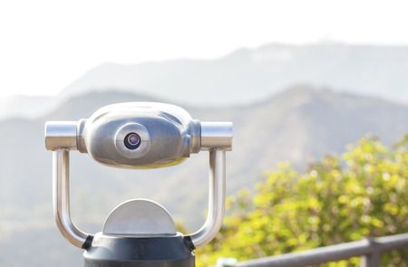 monocular: Monocular pointed at a mountain landscape, shallow depth of field.