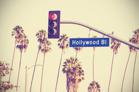 bl: Vintage retro toned  boulevard sign and traffic lights with palm trees in the background, Los Angeles, USA.