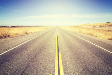 desert road: Vintage toned endless country road, travel concept picture. Stock Photo