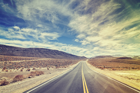 Vintage stylized endless country highway in Death Valley, California, USA. Stock Photo