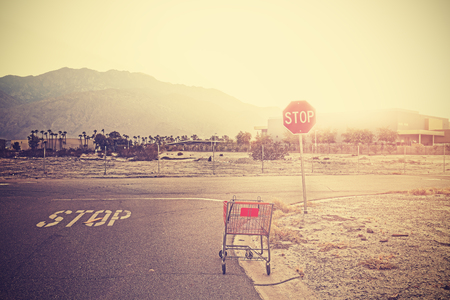 Retro toned empty shopping trolley left on street at sunset, Palm Springs, USA. Stock Photo