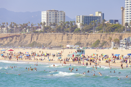 20th century: Santa Monica, USA - August 22, 2015: Beach full of people during peak season. Santa Monica had become famous resort town by the early 20th century.