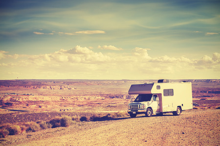 Retro toned camper parked by canyon, family vacation concept, USA.