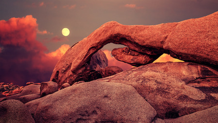 joshua tree national park: Purple sunset and rising moon over arch in Joshua Tree National Park, California, USA.