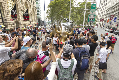 charging bull: New York, USA - August 16, 2015: Tourists taking pictures of the Charging Bull in Bowling Green Park, Financial District in Manhattan.