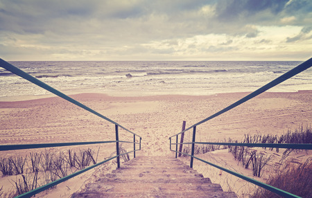 Vintage toned wooden stairs on a beach.