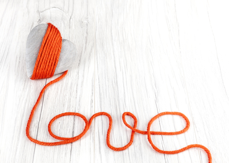 adultery: Wooden heart with red yarn love sign, space for text. Stock Photo