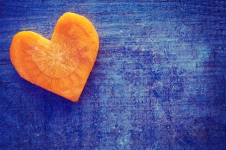 imperfection: Vintage stylized heart made of carrot on grunge background, space for text.