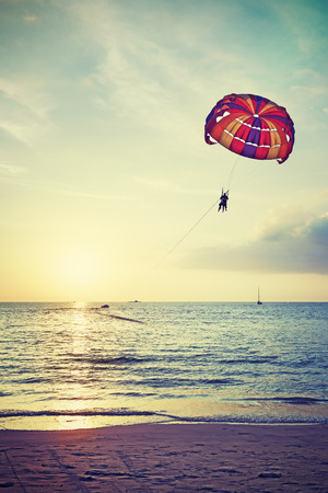 langkawi island: Retro stylized paragliders at sunset, summer adventure concept, Langkawi Island in Malaysia.