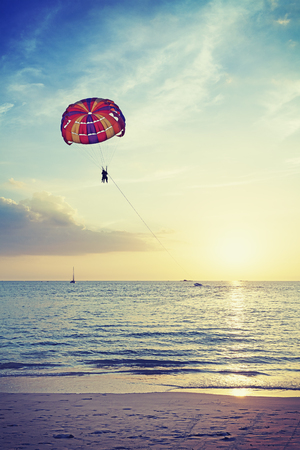 langkawi island: Vintage stylized paragliders at sunset, summer adventure concept, Langkawi Island in Malaysia.