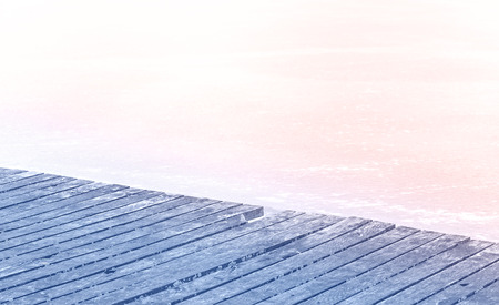 rose quartz: Rose quartz and serenity colors stylized wooden pier on frozen lake, space for text.