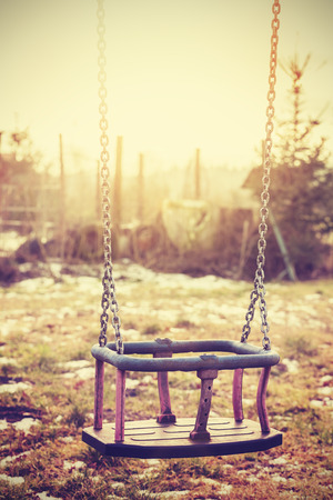 neglected: Vintage stylized an old neglected empty swing, shallow depth of field. Stock Photo