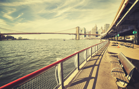 hudson river: Retro stylized Hudson River bank with bench and Brooklyn Bridge in distance, NYC, USA. Stock Photo