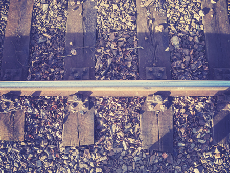 filtered: Retro filtered photo of railway track with wooden sleepers.