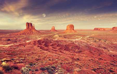 Monument Valley after purple sunset with full moon, USA.