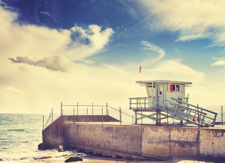 Retro toned picture of lifeguard tower at sunset, California, USA.