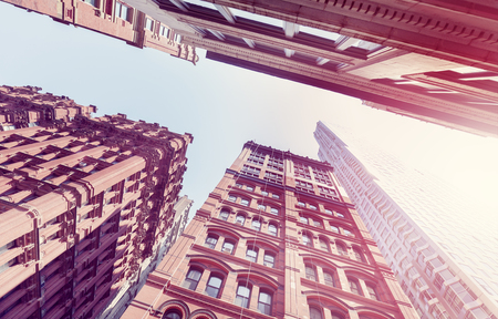 old new york: Vintage toned old and new buildings in Manhattan at sunset, looking up, New York City, USA.