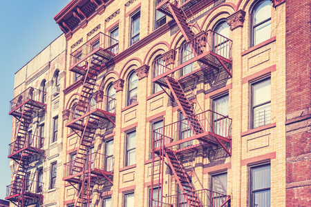 fire escape: Old film retro toned photo of New York building with fire escape ladders, USA.