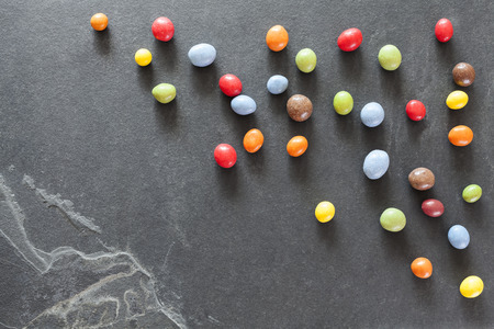 food background: Colorful candy on a dark stone background. Stock Photo