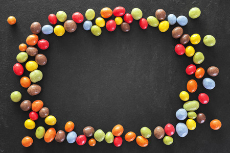 schist: Colorful frame made of candy on a dark stone background, space for text. Stock Photo