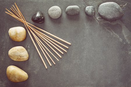 schist: Retro toned stones on slate background with incense sticks, zen or spa and wellness background. Stock Photo