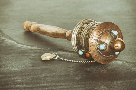 purify: Retro stylized old Tibetan prayer wheel used to accumulate wisdom and good karma and to purify bad karma, shallow depth of field.