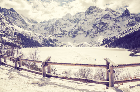 morskie: Vintage stylized frozen lake Morskie Oko in Polish Tatra Mountains at the end of March. This is the most popular mountain lake in Poland. Stock Photo