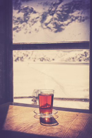cosiness: Retro old film style glass of hot tea on wooden table by a mountain shelter window, cosiness and comfort concept, shallow depth of field.
