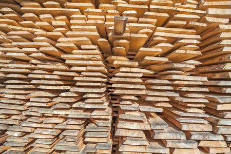 Stack of rough wooden boards in lumberyard.