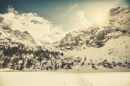 morskie: Retro old film style picture of Tatra Mountains against the sun, view from frozen Lake Morskie Oko, Poland. Stock Photo