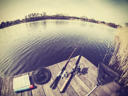 Retro stylized fisheye lens picture of fishing tackle on wooden pier.