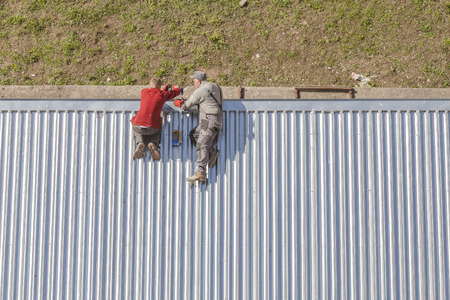corrugated metal: Szczecin, Poland - April 07, 2016: Workers repairing a store roof made of corrugated metal sheets, picture taken from above. Editorial
