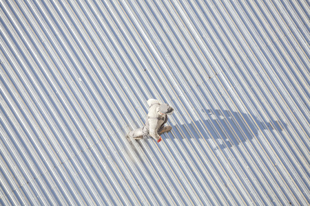 corrugated metal: Szczecin, Poland - April 07, 2016: Man inspecting a roof made of corrugated metal sheets after repair, picture taken from above.