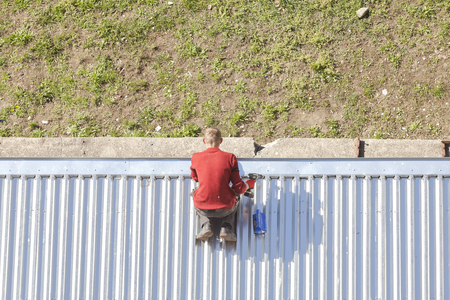 corrugated metal: Szczecin, Poland - April 07, 2016: Man with a drill reparing a store roof made of corrugated metal sheets, picture taken from above. Editorial