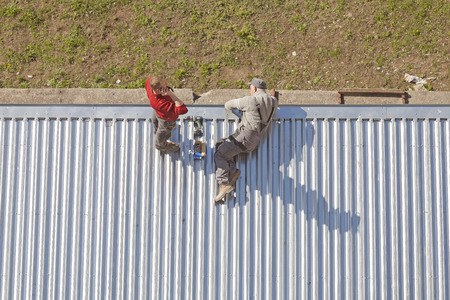 corrugated metal: Szczecin, Poland - April 07, 2016: Two men working on a store roof made of corrugated metal sheets, picture taken from above.