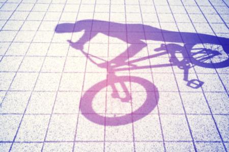 bmx bike: Retro toned blurred shadow of a teenager riding a bmx bike.