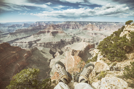 worn out: Retro old film stylized legs with worn out hiking shoes on the edge of the Grand Canyon, shallow depth of field, active holidays concept.