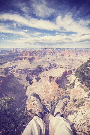 worn out: Vintage toned legs with worn out hiking shoes on the edge of the Grand Canyon, shallow depth of field, active holidays concept.